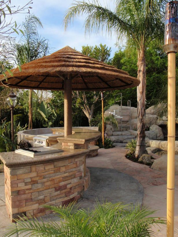 This tiki-styled outdoor kitchen features a cast-in-place concrete countertop on a natural stone bar.