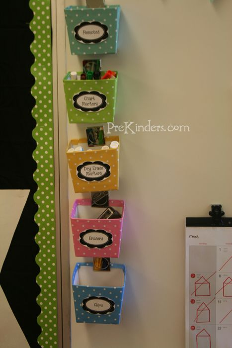 boxes from the Dollar Store, cover with scrapbook paper of your choice, and attached them to white board with magnetic clips. They hold remotes, chart markers, dry erase markers, erasers, and board clips.