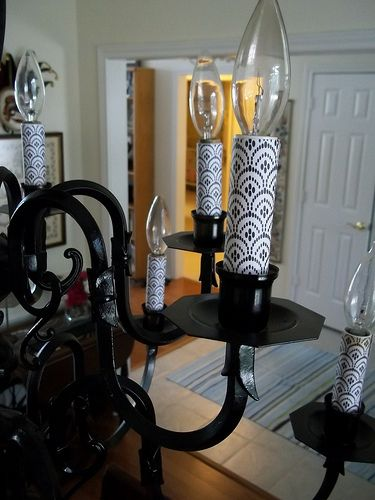 A spray painted old brass light fixture with scrapbook paper added to the candles! Awesome idea!