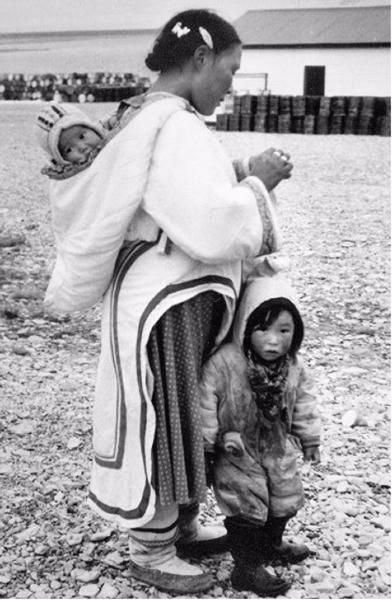 Inuit mother with one child in front of her and carrying one in her hood, Igloolik, N.W.T., [Igloolik (Iglulik), Nunavut], Sept 12, 1958. Library and Archives Canada / Credit: Charles Gimpel / Charles Gimpel fonds / e004923423