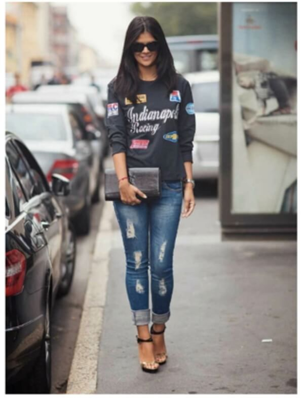 Синие джинсы, черный свитшот, клатч, черные очки и черные туфли на каблуках.