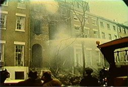 Weather Underground: Firefighters struggle to hose down the smoldering remains of a New York brownstone after bombing.