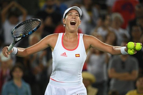 Garbine Muguruza Photos - Spain's Garbine Muguruza smiles as she is applauded by the crowd after winning her women's first round singles tennis match against Romania's Andreea Mitu at the Olympic Tennis Centre of the Rio 2016 Olympic Games in Rio de Janeiro on August 7, 2016. / AFP / Roberto SCHMIDT - Tennis - Olympics: Day 2