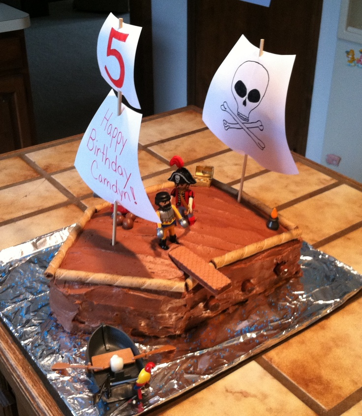 This is the pirate cake I made for my son's birthday! After trying to follow several others, I decided to try my own idea. It was SO simple! I baked 2 9x13 cakes and put one on top of the other with frosting. I cut off two corners to make it angled like the front of a boat. Then frosted it and  decorated it with Playmobile pirate figures, tootsie roll cannons on the side and cannon balls, pirouette rolled wafers around the edge, and a chocolate wafer cookie plank!
