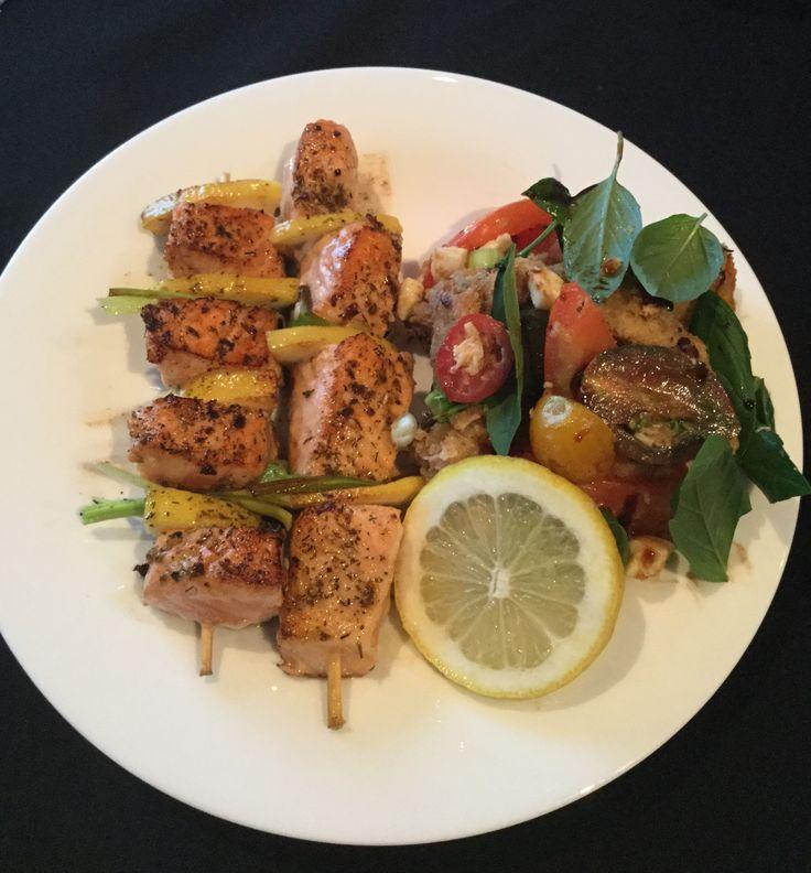 Saté van zalm met tomaten salade. Neem je zalm en kruid deze met viskruiden. Steek ze op een spiesje met citroenschijfjes tussen en bak ze krokant aan maar ze moeten wel smeuïg blijven binnenin. Neem stukjes stokbrood, en besprenkel deze met olijfolie en grof zout. Bak ze krokant in de oven. Snij tomaten en voeg 3ansjovisjes toe en olie en azijn. Snij event.ook wat mozarella maar dat is niet echt nodig. Roer er nog basilicum doorheen. Roer je croutons eronder en dien dadelijk op. Smakelijk.