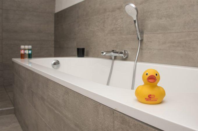 Deze badkamer met schuine muur werd echt handig ingericht met een bad een ruim lavabomeubel en - Imitatie cement tegels ...