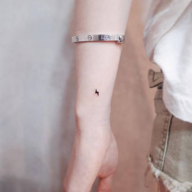 Tiny lightning bolt tattoo on the wrist.