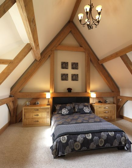 A bedroom with a large dormer window allowing the natural light to flood into the space.