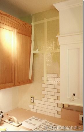 how to install tile backsplash...I'm liking the white cabinet to the right. Looks like cab with soffit. Both are same color and trimmed in molding