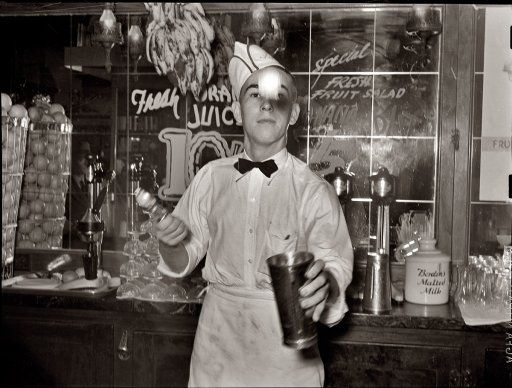 """February 1939. Corpus Christi, Texas. """"Soda jerker flipping ice cream into malted milk shakes."""" View full size. Photo by Russell Lee."""