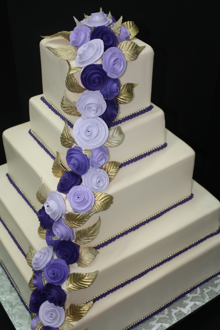Off-white wedding cake with different tier heights. Accented with a variety of purple shades of buttercream roses, gold fondant leaves and gold beading. www.sugarhillsbakery.com