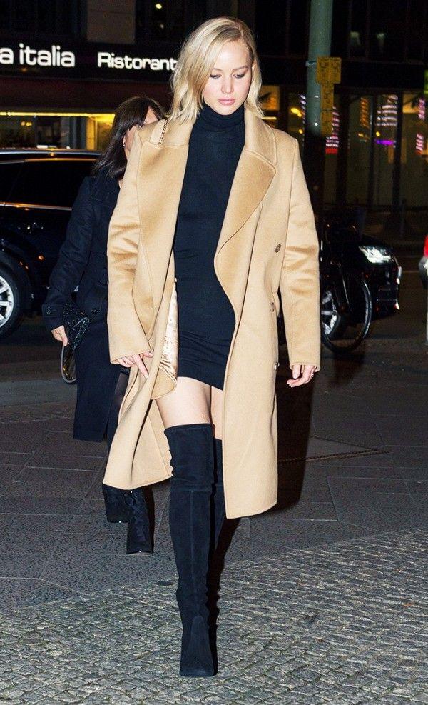 Jennifer Lawrence wears a black mini dress, camel coat, and thigh-high boots