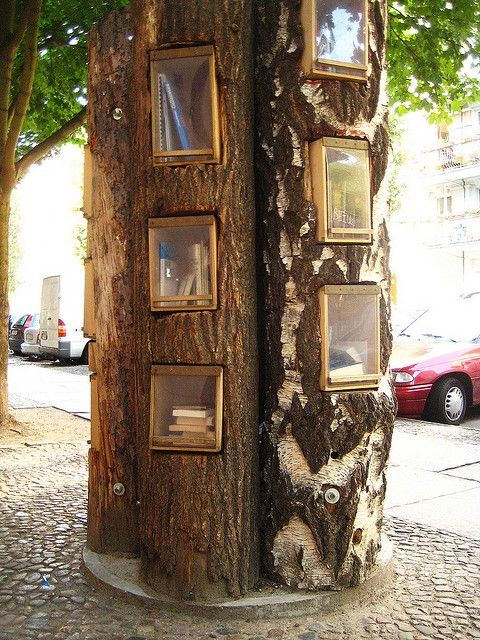 """Tree Library - Berlin, Germany. The project adopts the idea of putting up a bookcase in a public space, in which people could release their used books to be picked up by others. The """"libraries"""" are made from of hollowed out tree trunks. Travel Journeys"""