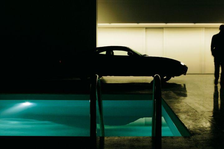 Dentro l'ex capannone industriale (un quadrato di 20 metri per lato e 10 di altezza) trovano posto la nuova architettura residenziale, la piscina e anche più di un'auto, come la Jaguar xK nera dell'architetto Marco Costanzi, che ha progettato per il fotografo Max Zambelli un'abitazione con uso di set fotografico.