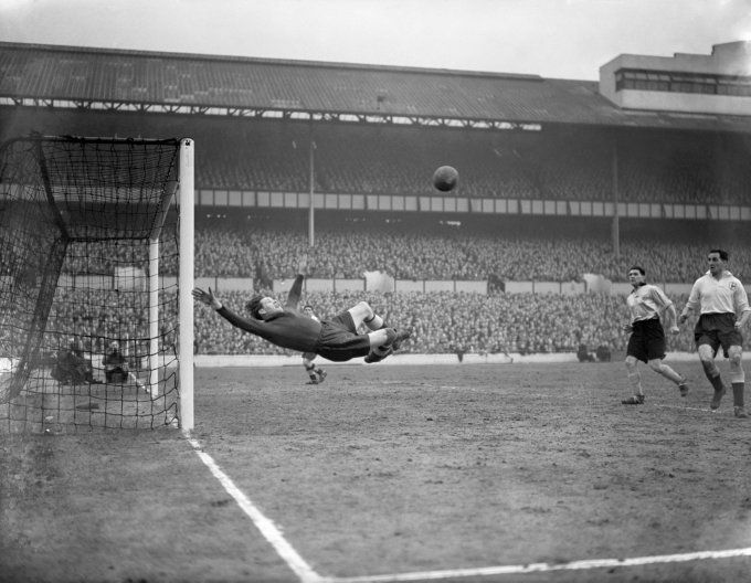 Tottenham goalkeeper Ted Ditchburn takes to the air to make a brilliant clearance against Hull City in the fifth round of the FA Cup, 1954