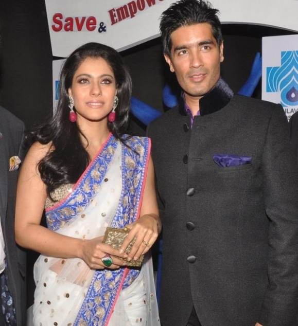 Kajol At Manish Malhotras Save The Girl Child Show, carrying an Invintage Ruby and Emerald clutch