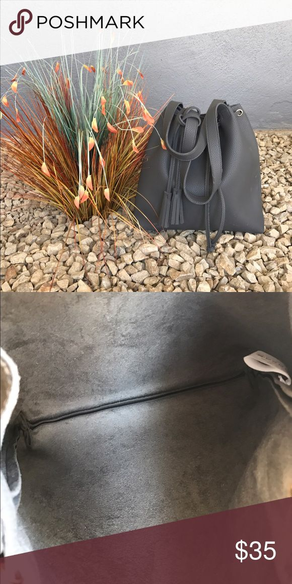 Gray Hobo Style Purse Gray is your new neutral!  Hobo bag with carry handle and shoulder strap. Gold tone grommets are on trend, as is the decorative tassel. Vegan leather exterior and suede interior. Bags Hobos