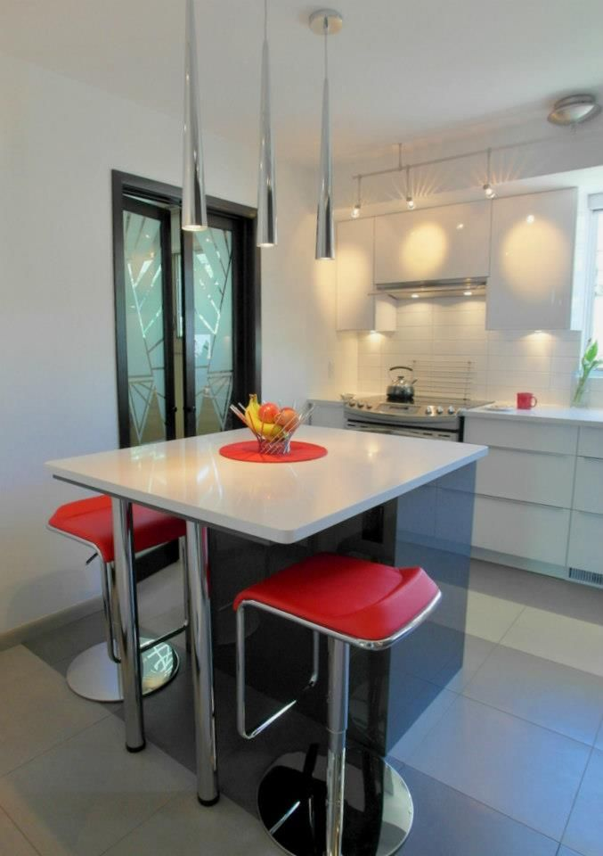 This kitchen island and space for 2 was overhauled by 7J Design to be modern and sleek along with some dramatic red.