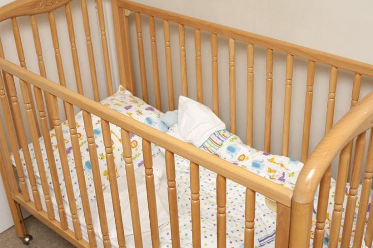 Empty wooden baby cot or crib with colorful pattern linen in the corner of a romom, close up view - free stock photo from www.freeimages.co.uk