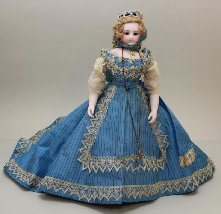 """Marie"". Provenance: These things were from brought from Paris by Uncle Charlie Hayes for Lena Fisbee Hayes about 1867-1868. Stationary blue eyes, closed mouth, pierced ears, (2) mohair wigs: honey blonde & gray; cork pate. Swivel head on bisque shoulder plate. Leather body with bisque lower arms. Dressed in turquoise silk tafetta gown with complimentary bonnet. Cotton petticoat, pantaloons, hoop skirt petticoat. Tan leather heeled shoes, lace socks. Stand. Comes with 2 pc. brown silk…"