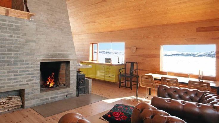 RENT DESIGN: Så enkelt og rent kan et moderne hytteinteriør bli. Gulv og vegger er av kvistfri furu, lerk i takpanel og peis av betongstein. FOTO: Jan Larsen