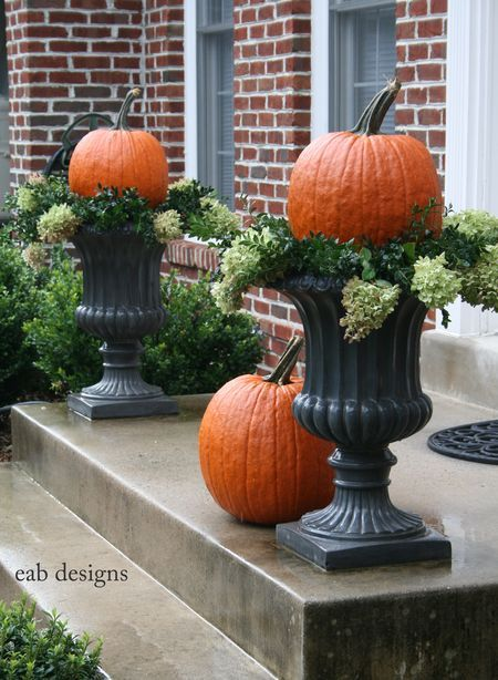 Yep, I'm doing this. Pumpkins on black urn planters. Also saw it with straw/corn husks (?) as filler.