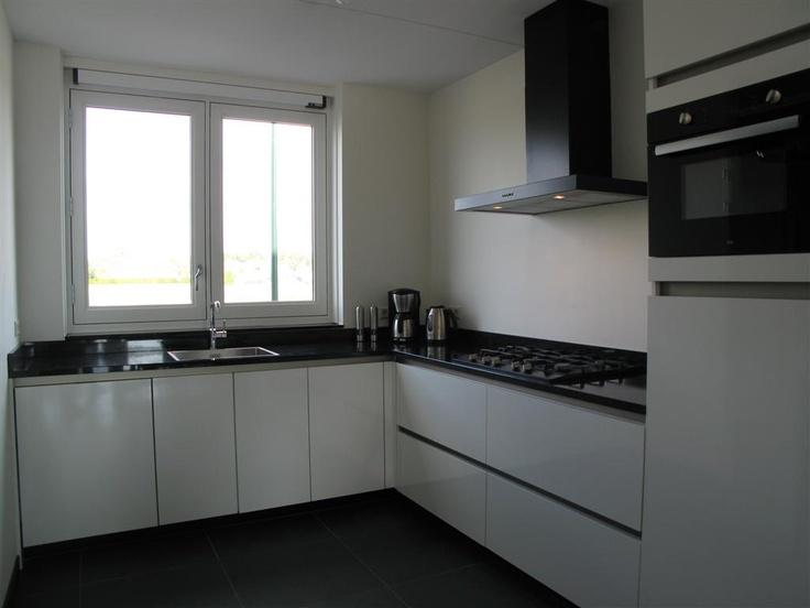 Moderne greeploze hoogglans keuken met zwart apparatuur @ETNA Keukenapparatuur en granieten werkblad.