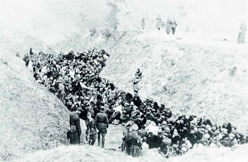 The Jewish population of Mizoch, town in Rivne region, awaiting execution at the bottom of a large ravine. October 14, 1942.