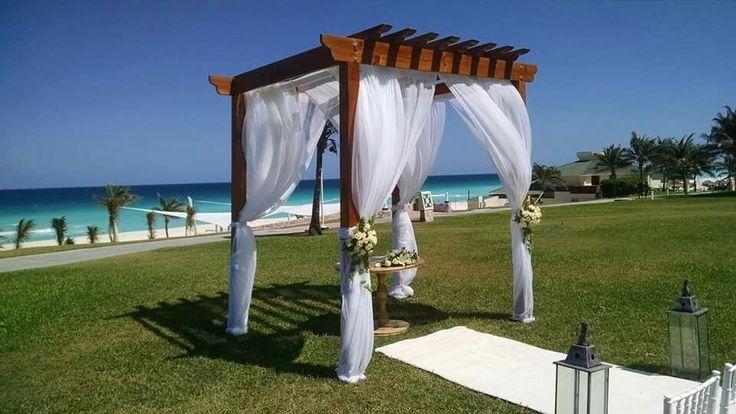 Perfecto harmony, pérgola ambientada con cortinaje blanco y detalles de flores.