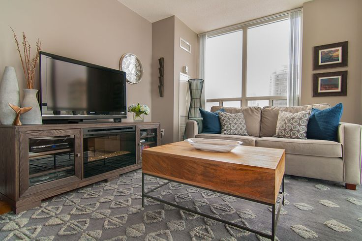 In this bachelor's condo, the warm wood tones helped to contrast the cool shades of grey and blue to create a cozy and inviting space around the big screen TV.