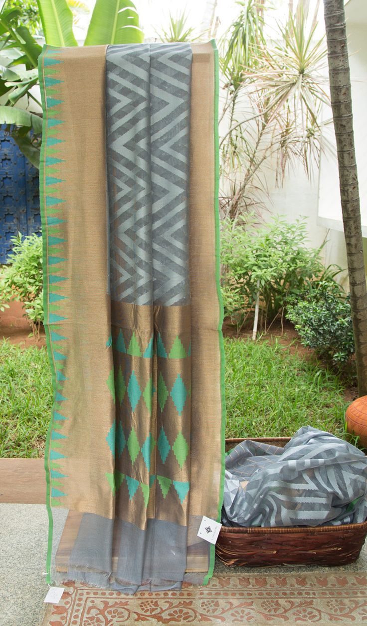 This benares net sari is light grey colored with herringbone texture woven in silver thread work all over. The border and pallu have a solid gold zari base with geometric patterns woven in teal blu…
