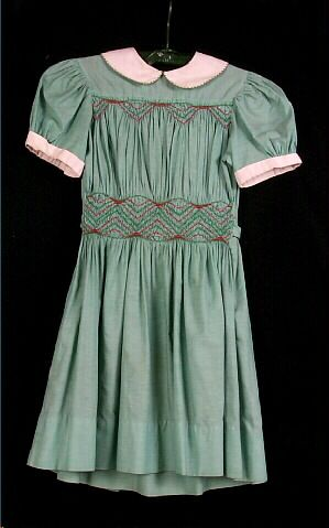Green dress with white cuffs and collar, smocked bodice and waist in red and green.