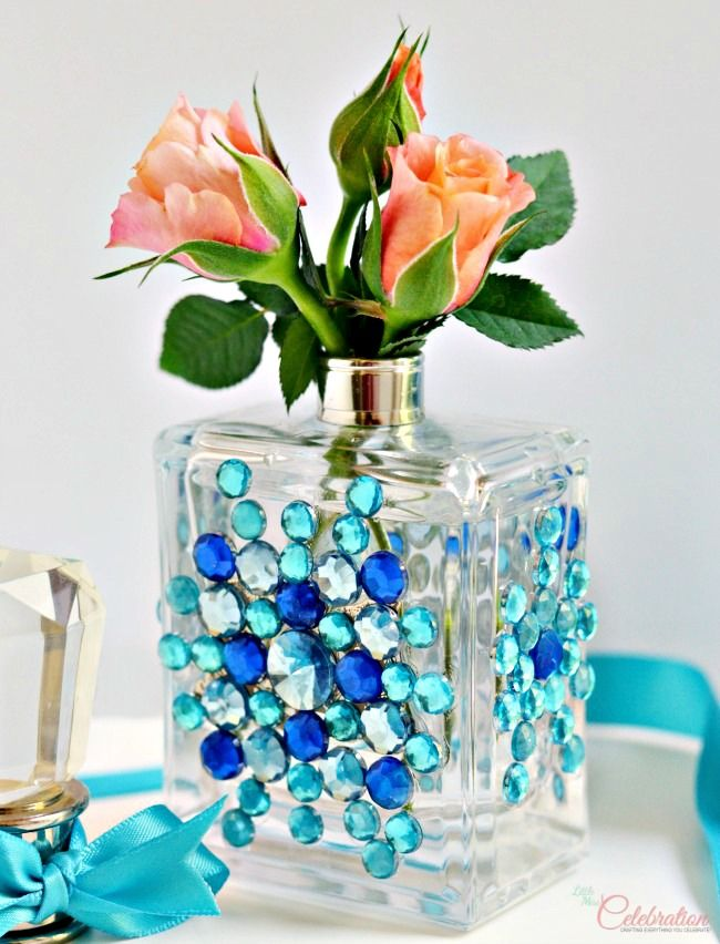 Don't toss that empty perfume bottle!  With some gems & glue, upcycle it into a pretty bud vase that doubles as a decorative piece, too! At littlemisscelebration.com