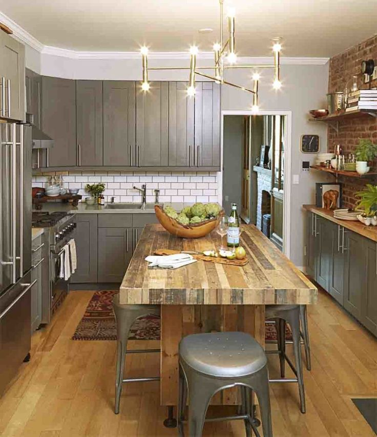 REINVENT THE KITCHEN TABLE Prep, serve, and entertain at an island that fits stools underneath, offering seating for a gathering of friends. The homeowners added iron legs to bring this butcher block piece to the right height.