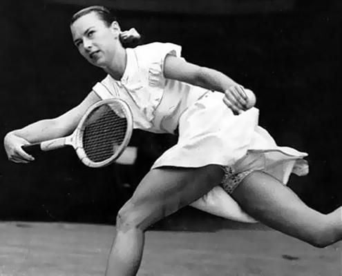 """1949   """"Gorgeous"""" Gussy Moran asked the Wimbledon organizers if she could wear colored clothing. Her request was turned down, so tennis fashion designer Ted Tinling created a dress incorporating lace-trimmed knickers which even triggered a debate in parliament. Photographers lie flat on the ground in order to shoot her knickers."""