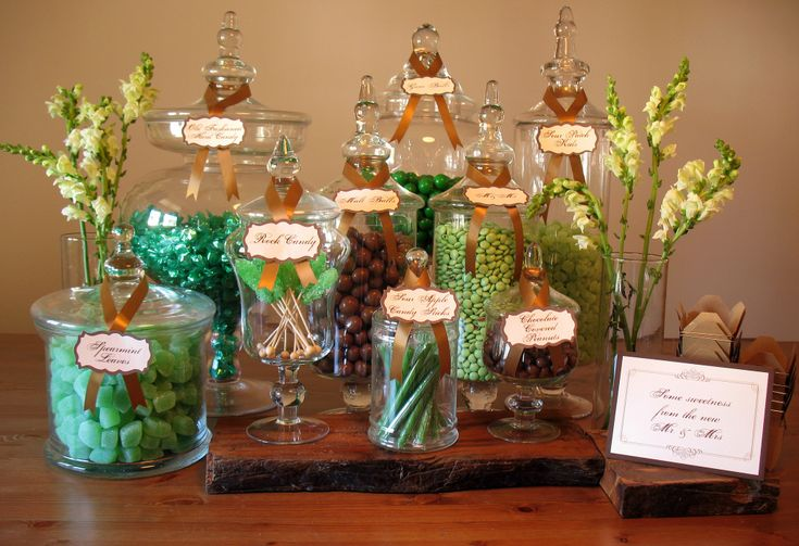 """This candy buffet was designed around the colors green and brown with a the theme of an """"enchanted forest"""". We used some props for enhancement. We used wooden slabs as risers, which gav…"""