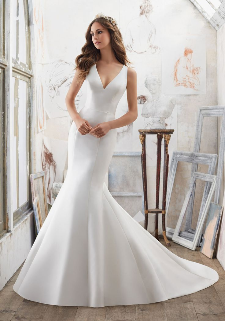 This Mori Lee Blu 5506 Marlena sleeveless Larissa satin wedding dress with a V-neckline and a sleek trumpet silhouette has a semi-open illusion cutout back. Crystal beaded straps lead from the back shoulders. Covered buttons accent the crystal beaded illusion back and run the full length of the skirt to the tip of the chapel train.