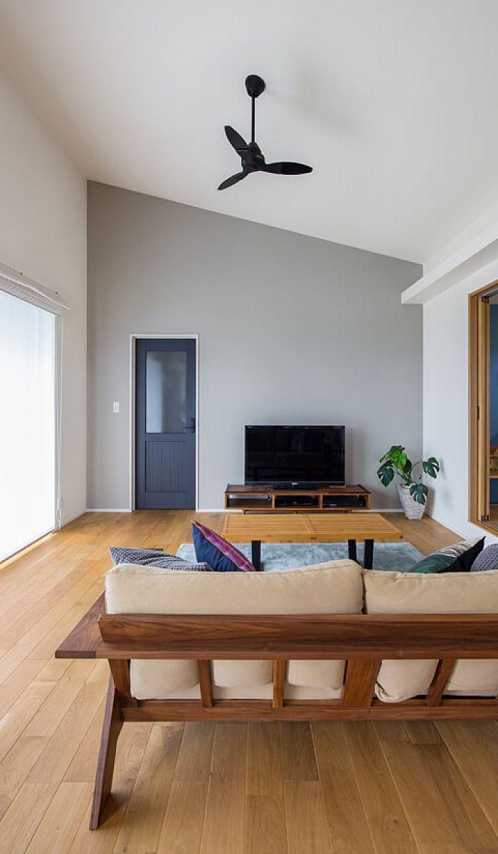 勾配天井を配した開放的なリビング空間 グレー色のアクセントクロス