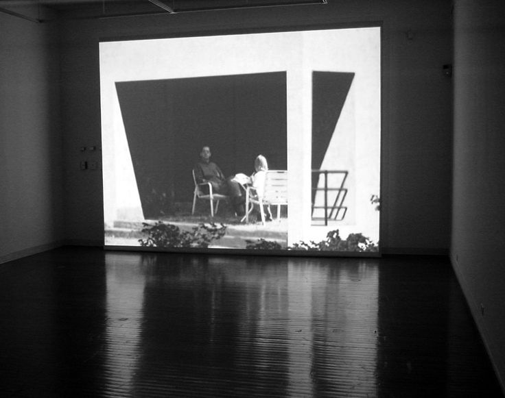 (Carl & Julie), 2000 - David Claerbout This video shows a man and a girl seated in the shade at their holiday house. The girl is busy drawing, her back turned to the spectator. The man looks at the camera. When a visitor enters the room where the work is displayed, a sensor causes the girl to turn her head, notice the visitor's presence, and then return to drawing.