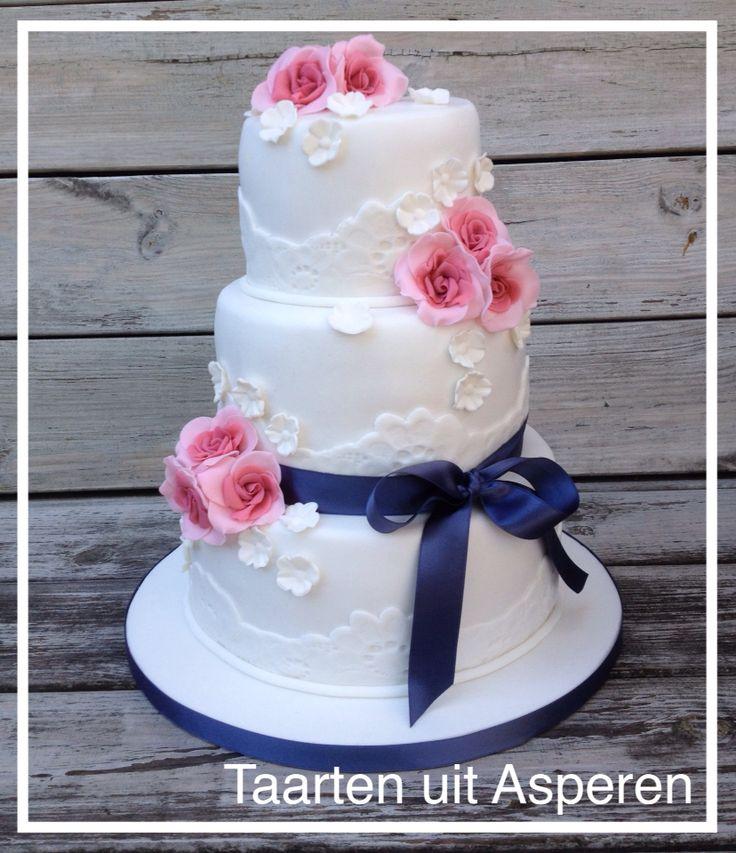 Bruidstaart met kant en roze rozen, donkerblauwe strik