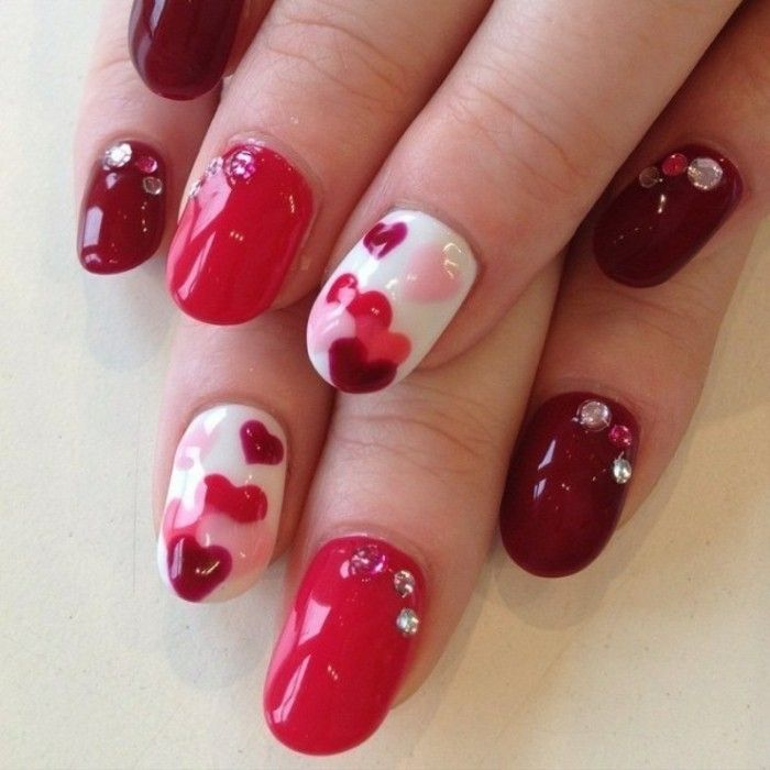 wine red, dark hot pink and white nail polish, decorated with rhinestones and painted hearts
