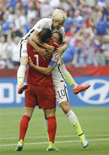 United States' Carli Lloyd, right, celebrates with goalkeeper Hope Solo (1) and Megan Rapinoe, top, after Lloyd scored her third goal against Japan during the first half of the FIFA Women's World Cup soccer championship in Vancouver, British Columbia, Canada, Sunday, July 5, 2015. (AP Photo/Elaine Thompson) ▼6Jul2015AP Enveloped in controversy, Solo leaves as World Cup winner http://bigstory.ap.org/article/f0faa35fa36642328c445269ac2d5689 #2015_FIFA_Womens_World_Cup…
