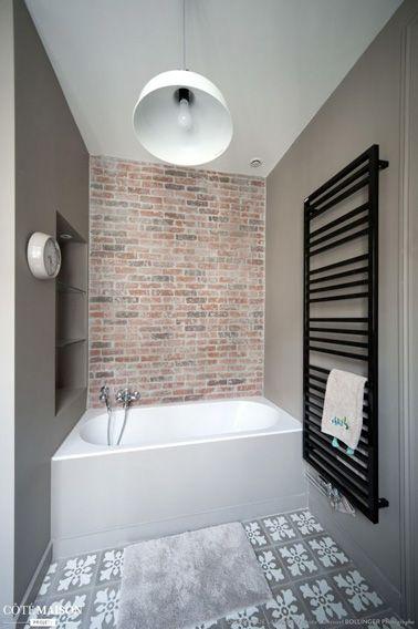 On les oublie bien souvent, mais les murs doivent être aussi utilisés pour exploiter et maximiser l'espace d'une petite salle de bain. Carreaux de ciment et mur de brique embellissent la déco de cette salle de bain taupe où une petite niche aménagée au dessus de la baignoire sert à ranger les produits de bain et de beauté. Autre astuce déco imparable pour gagner de la place dans une petite salle de bain, le sèche-serviette électrique mural préféré à l'encombrant sèche-serviette sur pied. Une…