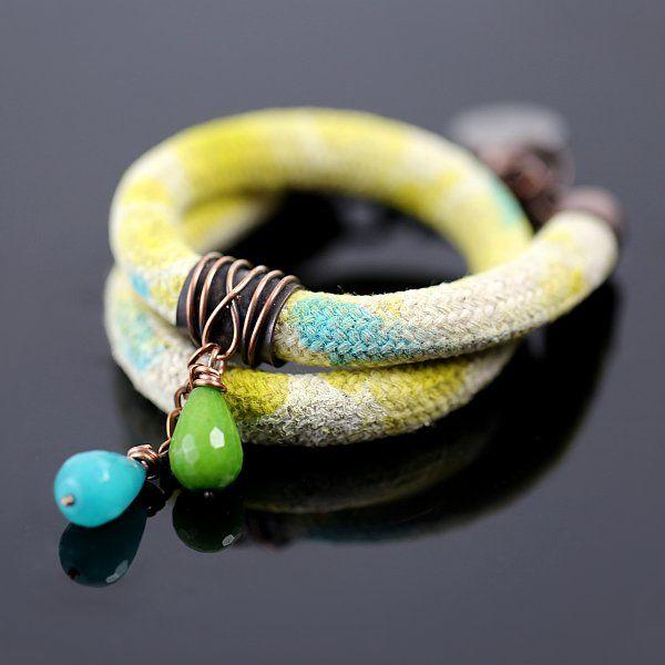 Efektowna bransoleta zawijana na rękę, wykonana z miedzi, lnu i jadeitów. Samodzielnie barwiony lniany sznur o turkusowo – zielonkawych odcieniach ozdabia pierścień z wiszącymi kroplami jadeitu (jasno zieloną i morsko – turkusową). Idealny prezent na każdą okazję: urodziny, walentynki, pod choinkę.
