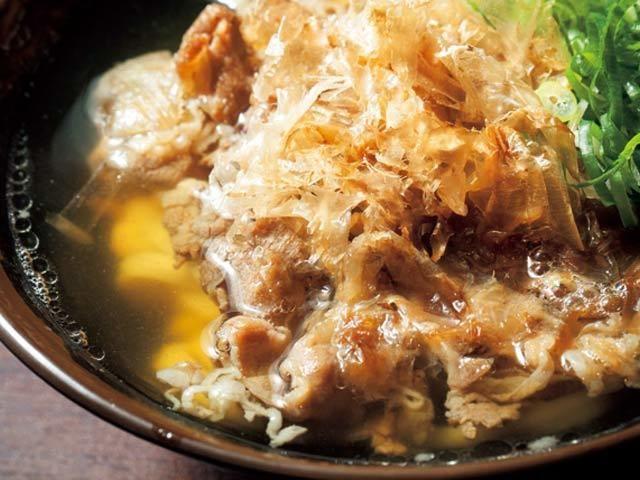 《 神田 》肉うどん(中)¥750  出汁に寄り添うあっさり味が素晴らしい!  『香川一福』  神田  香川の人気うどん店『一福』が昨年、神田にオープン。ウルメとさばを主体とした出汁と、さぬきうどんよりも細めに仕上げたうどんで、瞬く間に人気店の仲間入りを果たした。   「カレーうどん」などとともに人気なのがこの「肉うどん」。出汁の香りを邪魔しないようにと、US産の牛を使用。玉ねぎと出汁、しょうゆなどを半日かけて煮込むことで、出汁との調和を高めている。一口食べれば、さっぱりとした肉の味わいと玉ねぎの甘みが口に広がる。香川の乾物店から仕入れるという鰹節も一興。   食べるごとに肉と出汁がまろやかになり、あぁ食べ終わりたくない、と心から願うはず。数量限定なので、確実に食べたい人は早めの来店がベター。