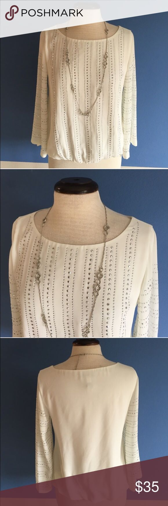"""Alfani Cream Studded Blouse Wow!   This blouse is sure to make a statement.  The studs highlight the front and arms of the top. The back is solid cream. The elastic bottom provides the perfect fit. Material:  100% Polyester.  Measurements:  Length- 23""""/Bust - 19"""" Alfani Tops Blouses"""