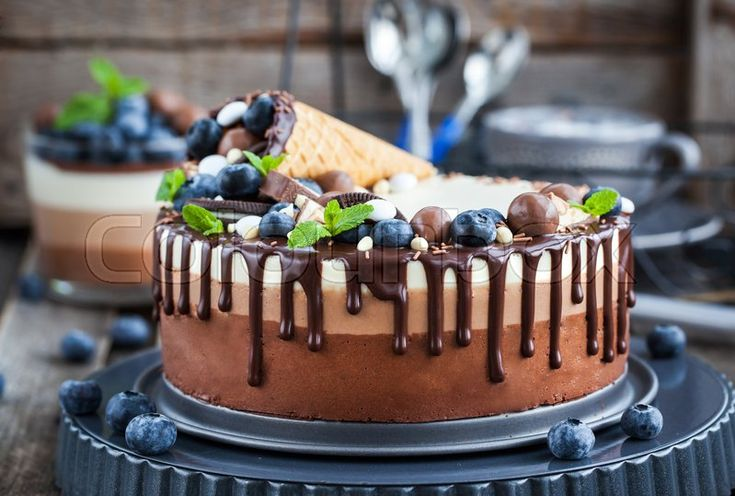 Food Photography. Delicious three chocolate mousse cake decorated with waffle cone, fresh blueberry, mint, candies and frosting. Photo by Ekaterina Smirnova, follow her on https://www.colourbox.com/supplier/ekaterina-smirnova-80703