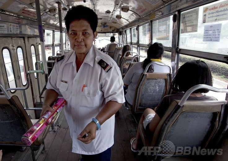 タイ・バンコク(Bangkok)のバス車内で運賃を徴収する車掌のワッチャリ・ビリヤさん(2014年4月28日撮影)。(c)AFP/PORNCHAI KITTIWONGSAKUL ▼8Jun2014AFP 大人用おむつ着用しないと働けない…、待遇改善求めるタイのバス車掌ら http://www.afpbb.com/articles/-/3016946 #Bangkok #Bus_conductor