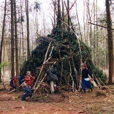 Kinderen bouwen een hut in het Speelbos, Sallandse Heuvelrug, Nijverdal. Vol kuilen, hellingen, bruggen, slingertouw en een klimboom.