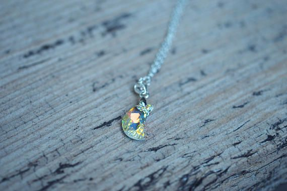 """This necklace features a stunning iridescent Swarovski crescent moon pendant, hung from a .925 sterling silver chain with a matching lobster clasp. The moon flashes a rainbow of colours in the sun, particularly rich yellows and vibrant blues (pictured). When not in bright sunlight, the colours are more muted and present overall as a warm golden orange hue. This is intended as a one sided pendant, as the other side is covered in a special coating which causes the """"aurora borealis"""" rainbow…"""